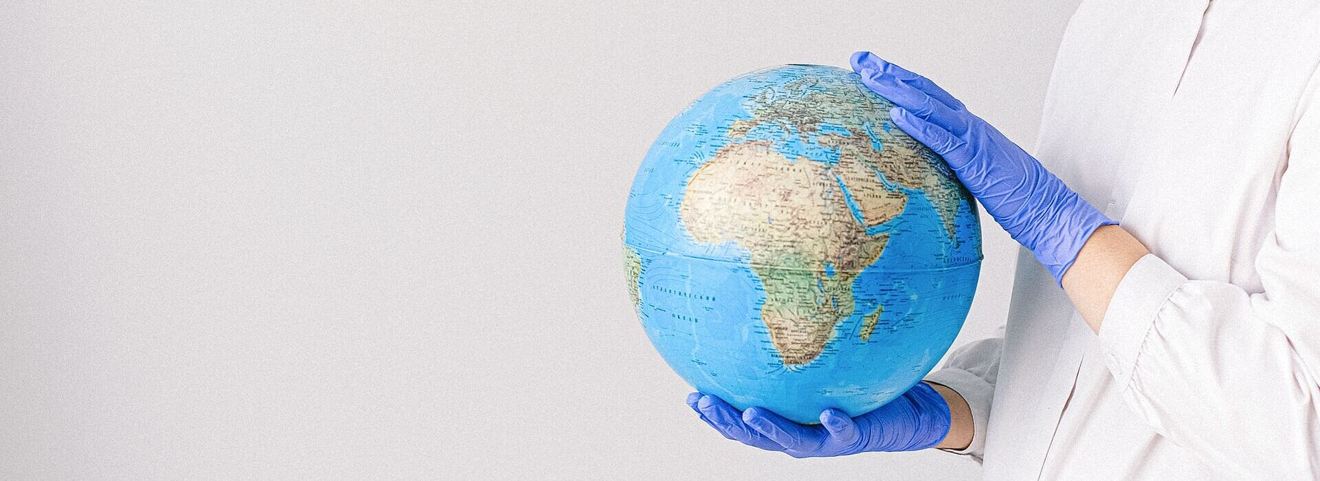 mulher de luvas e máscara segurando um globo do planeta