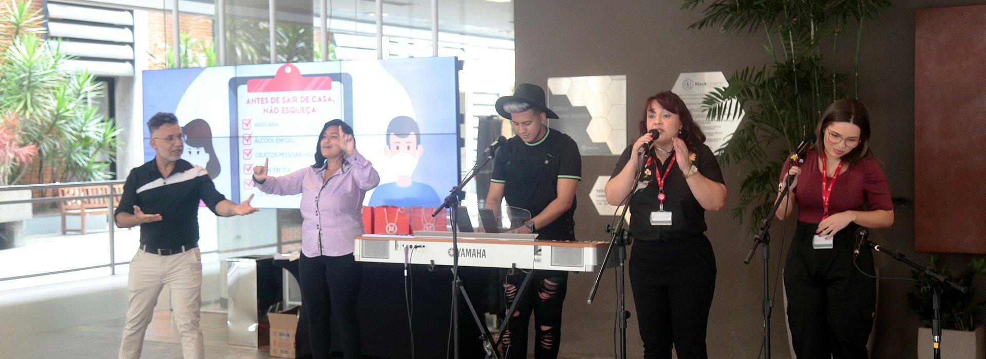 na imagem, cinco pessoas com instrumentos musicais se apresentam