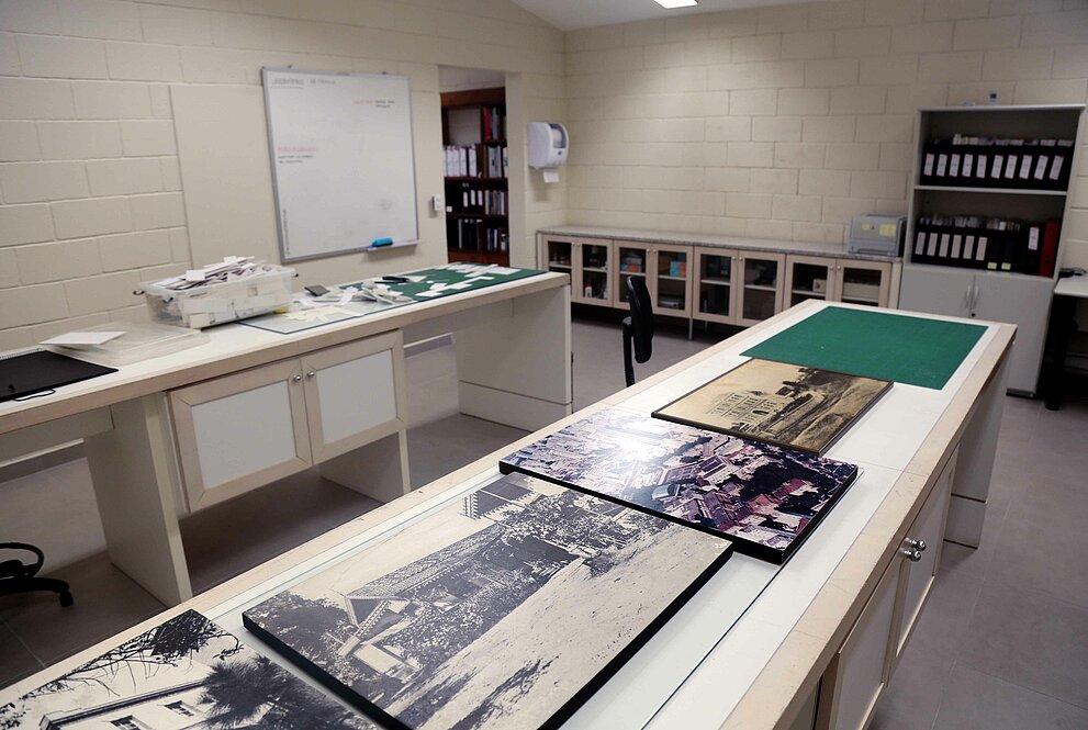 sala com obras do acervo de imagens sobre grandes mesas