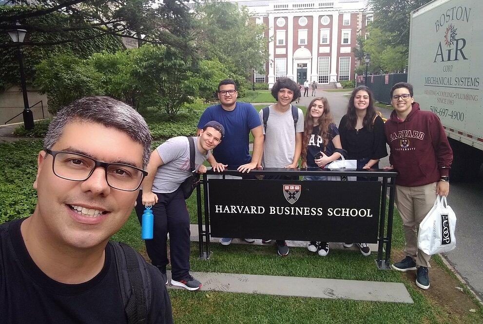 Selfie do professor Anderson com a turma de mackenzistas na placa de Harvard, com a universidade atrás.