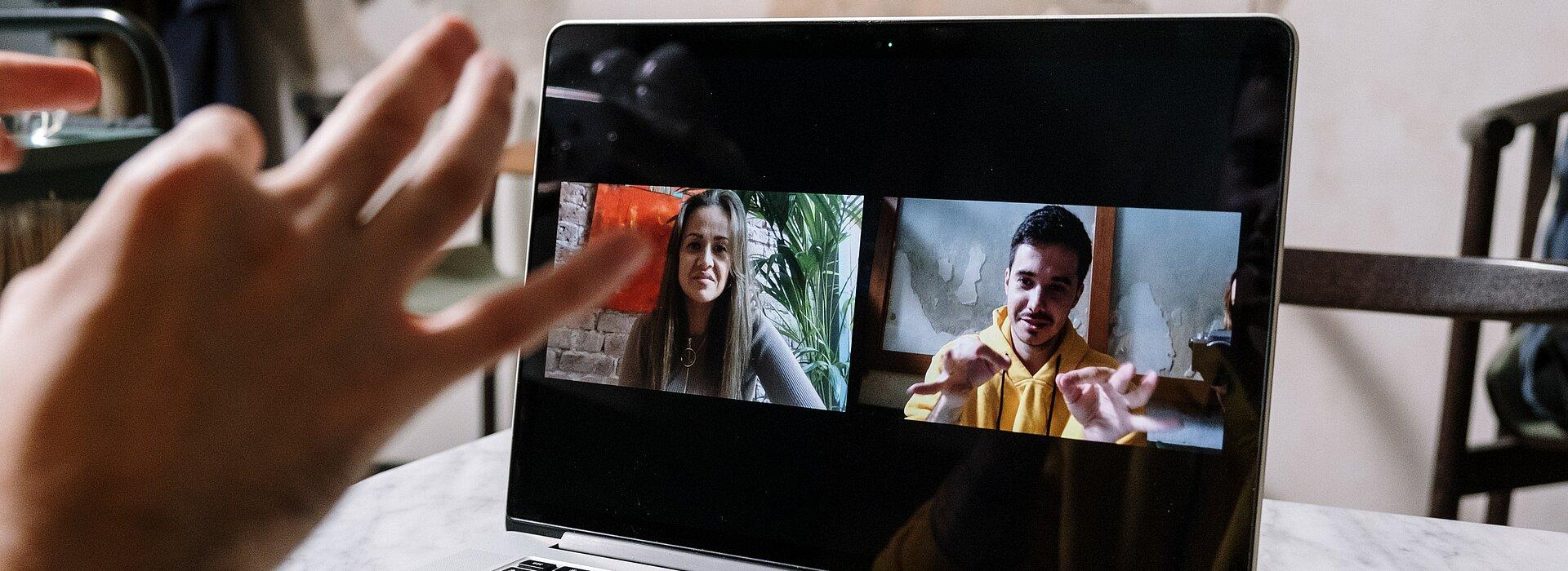 A imagem mostra um homem em uma videochamada com uma menina, eles estão converrsando em libras e a foto foca no notebook, mostrando a conversa.