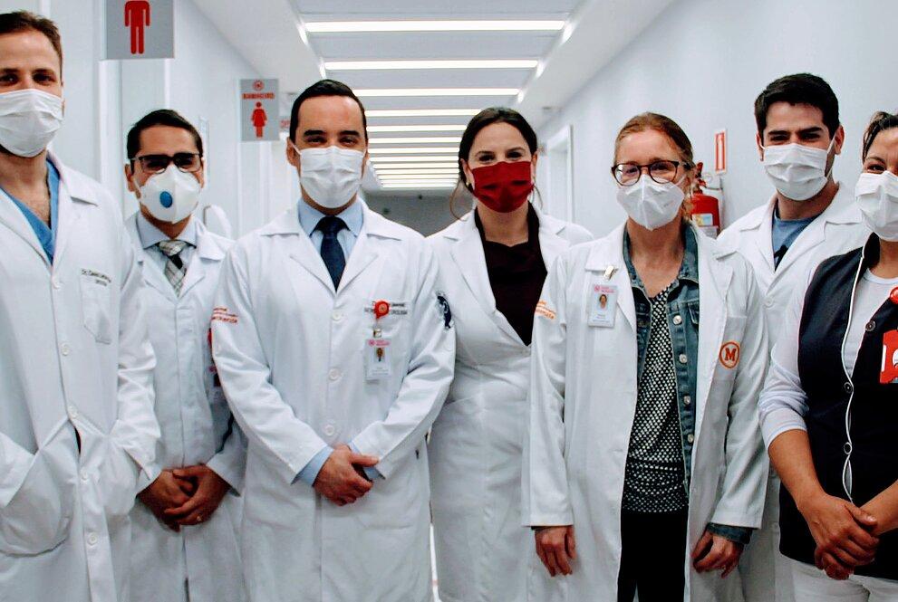 Na imagem, sete pessoas entre homens e mulheres, posam para foto num corredor claro de hospital. As pessoas vestem jalecos e uniformes com símbolo do Mackenzie e estão usando máscaras