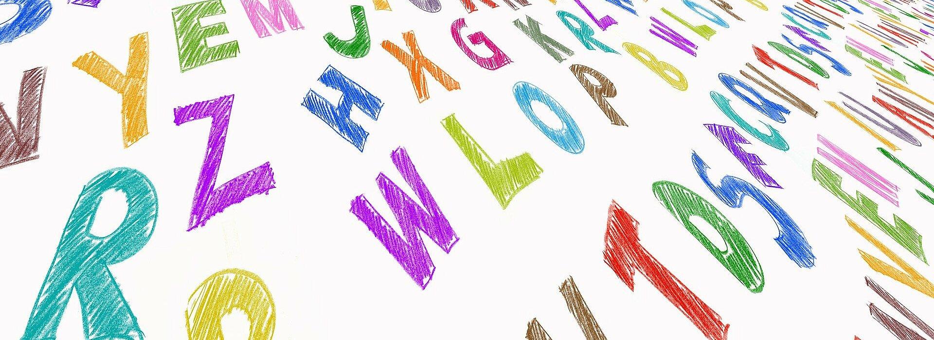 Diversas letras do alfabeto estão espelhadas pela foto. Elas têm diferentes cores e formatos.s