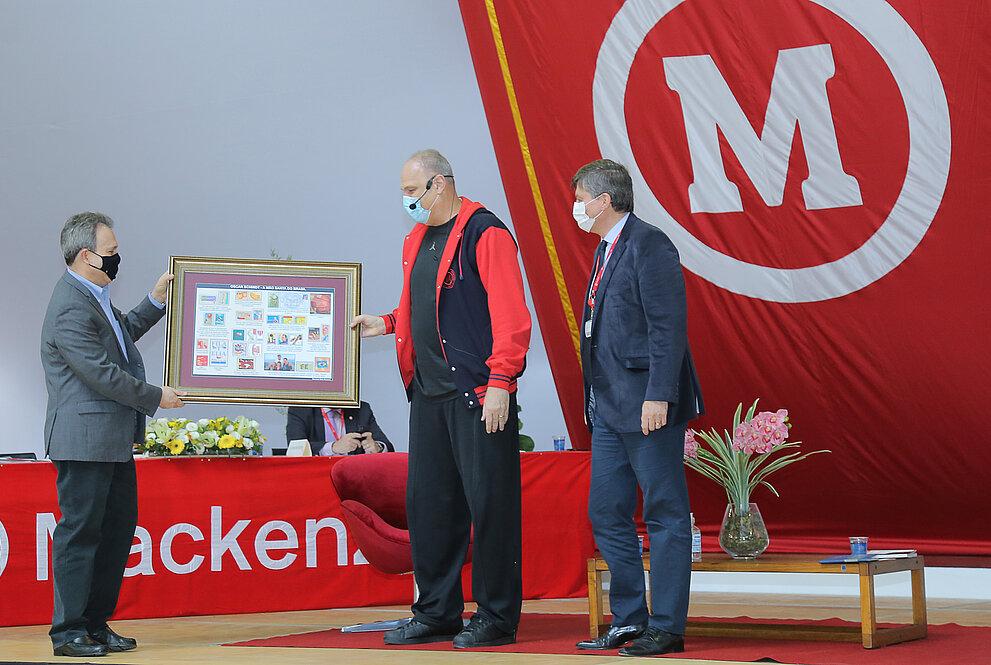 Dois homens entregam quadro para homem alto