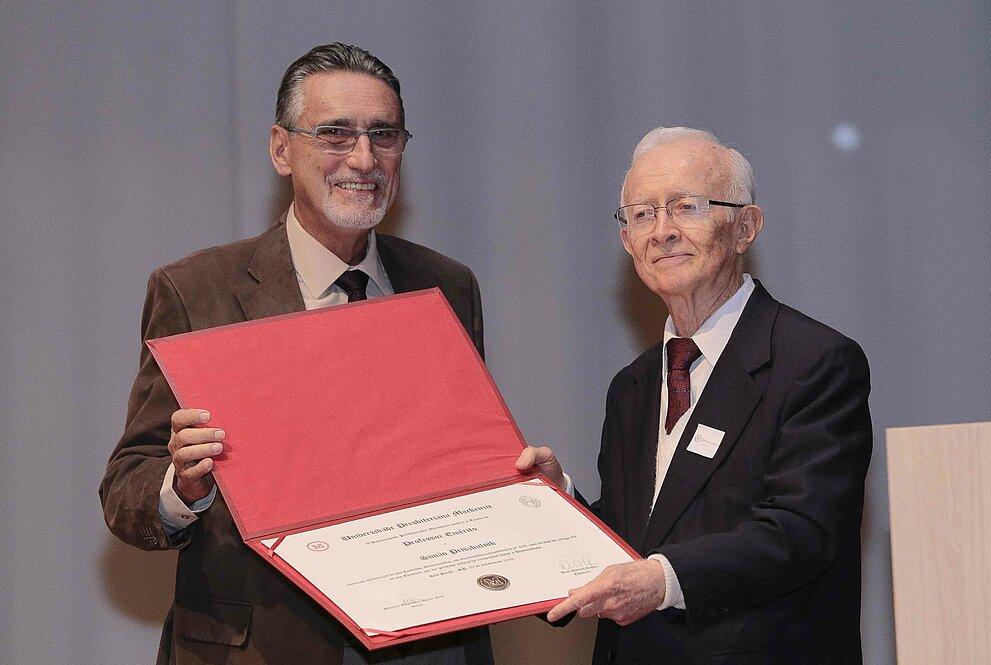 Um homem entrega um diploma para outro homem idoso