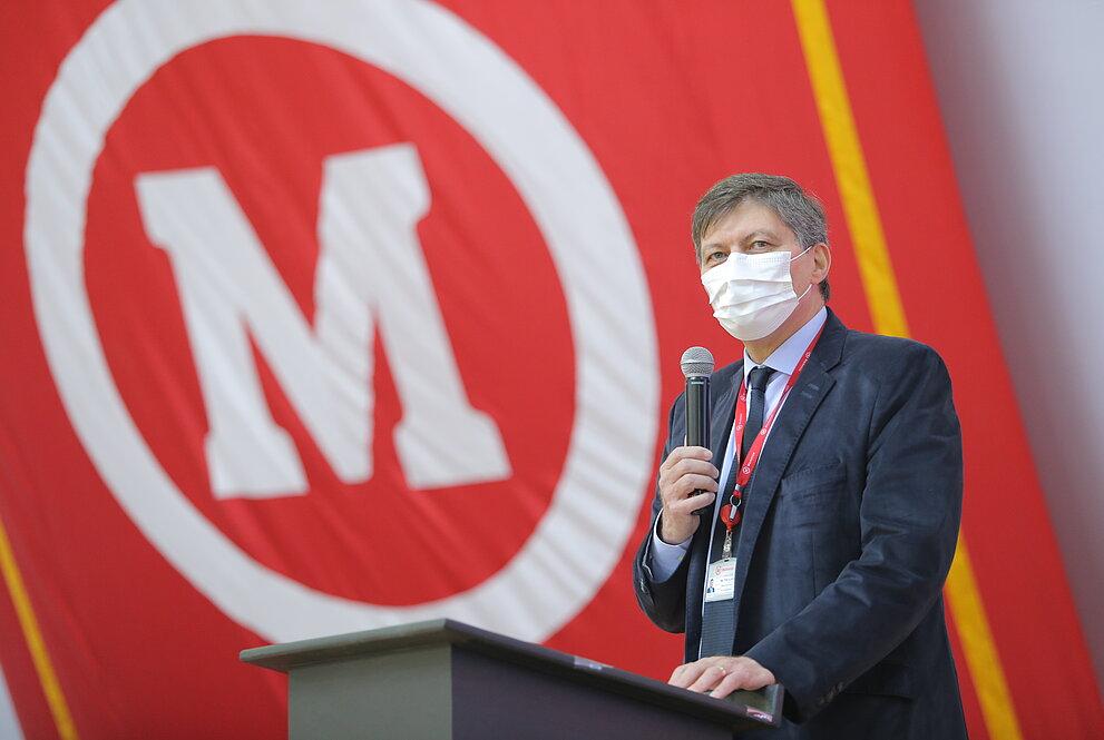 Homem de terno falando ao microfone com bandeira do mackenzie ao fundo