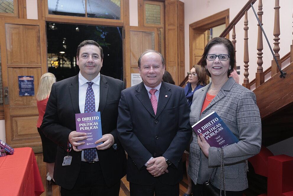 três pessoas em pé, mostrando livros