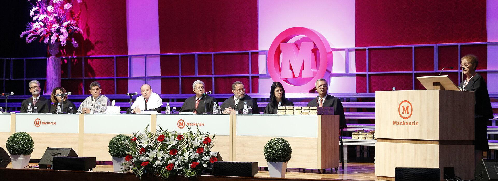 Autoridades sentadas à mesa enquanto a paraninfa discursa ao púlpito