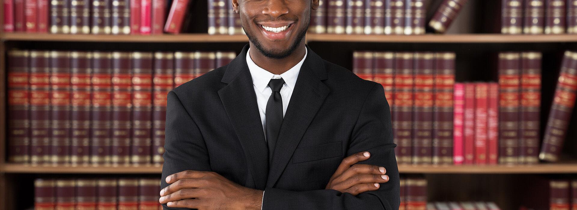 homem sorrindo de braços cruzados em frente uma estante de livros