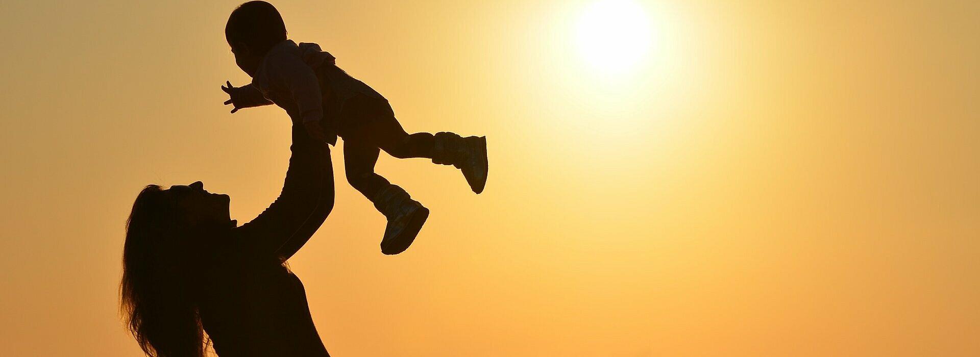mulher segura seu filho no alto na praia com por do sol ao fundo