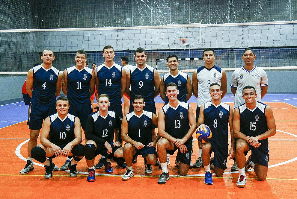 Competidores da Escola Naval posando para foto, em frente à rede de voleibol.