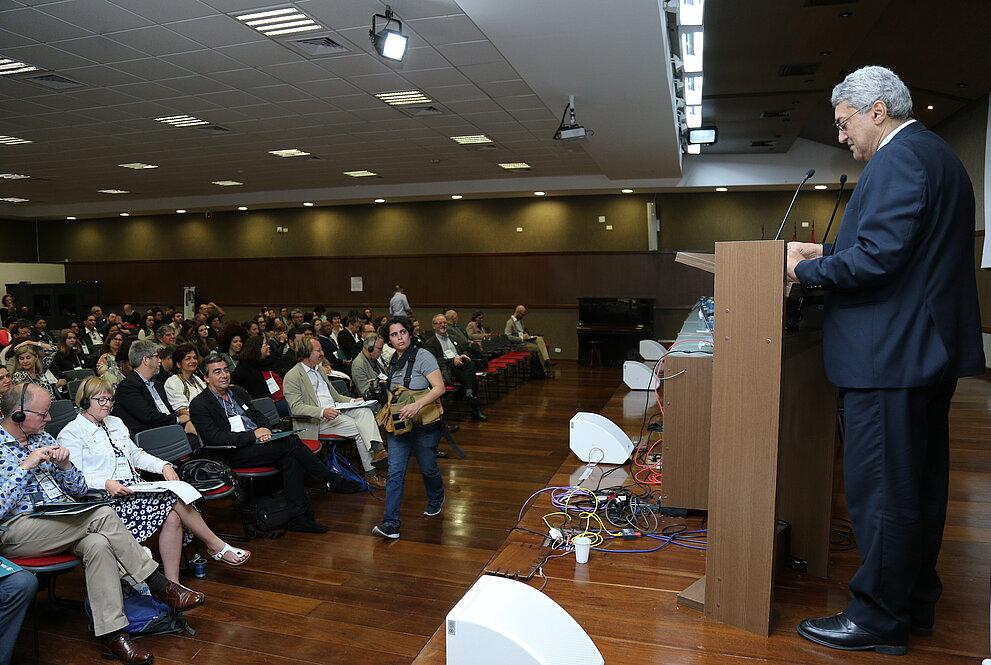 Palestrante Paulo Batista Lopes em frente a um auditório lotado