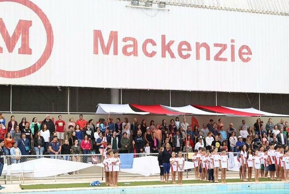 alunos posicionados em frente a piscina e com uma plateia ao fundo