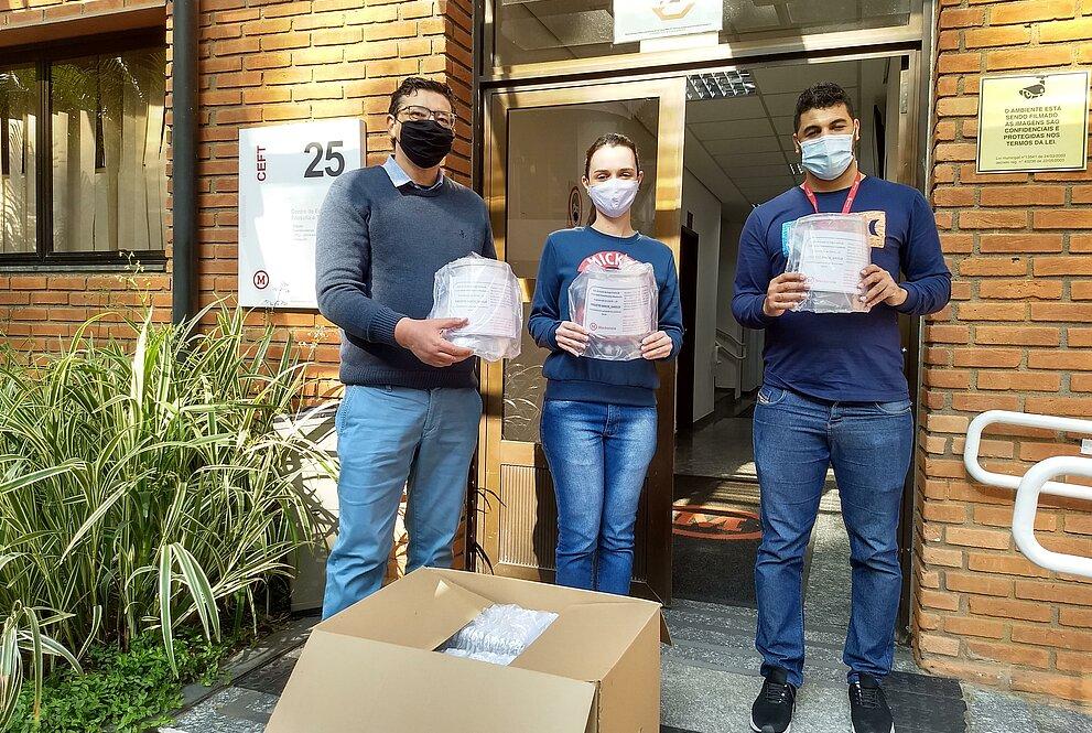 Três pessoas de pé, usando máscaras, em frente a uma parede de tijolos vermelhos seguram face shields