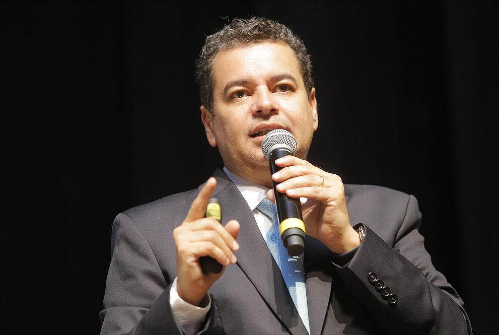 Homem falando com microfone na mão