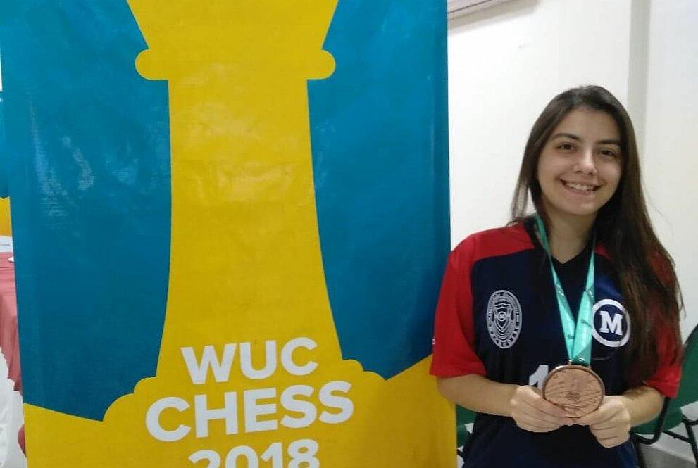 Julia Alboredo ao lado de banner da competição WUC Chess 2018