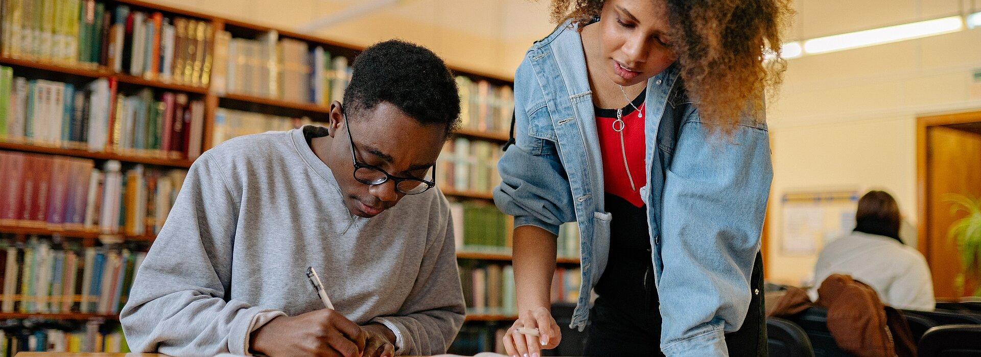 Um homem negro está sentado escrevendo e uma mulher negra está em pé olhando os materiais ao seu lado. Eles estão em uma biblioteca.