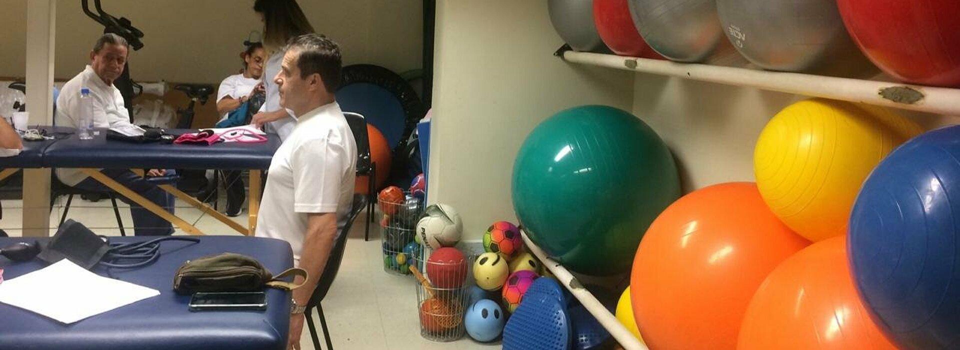 Do lado direito da imagem tem uma parede com bolas de ginástica de várias cores e do lado direito está um homem sentado fazendo exercícios ao mesmo tempo que outro homem também faz no fundo da imagem