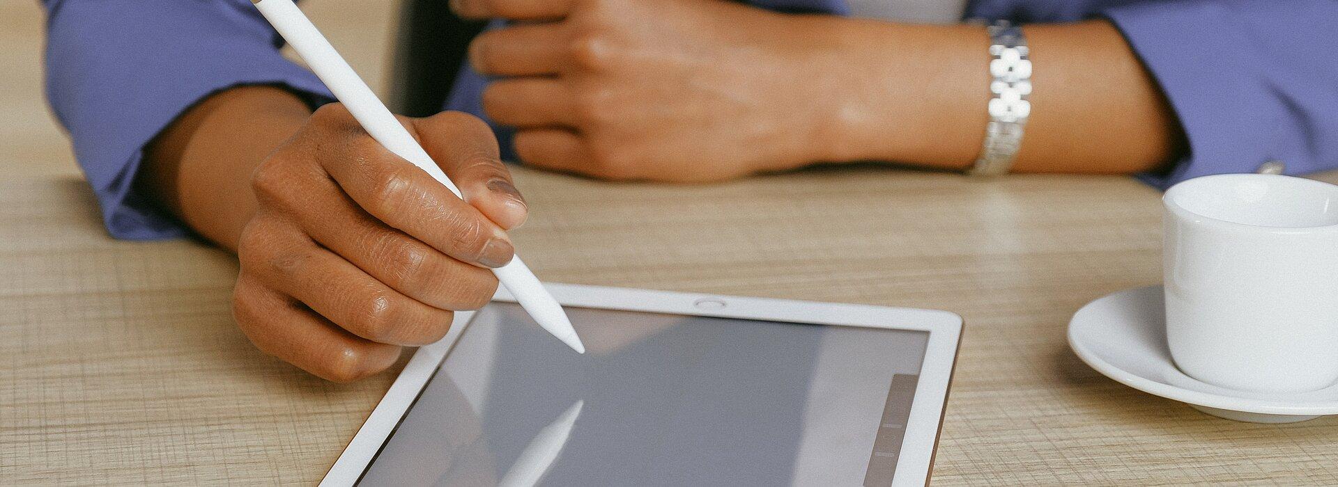 A foto mostra os braços de uma mulher apoiados sobre uma mesa. Ela está usando um tablet, com uma caneta. Uma xícara também está ao seu lado. Ela está usando um blazer, o que remete à negócios.