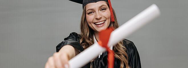 Na foto, uma menina mostra seu diploma para a câmera. Ela está de beca, com capelo e está sorrindo.