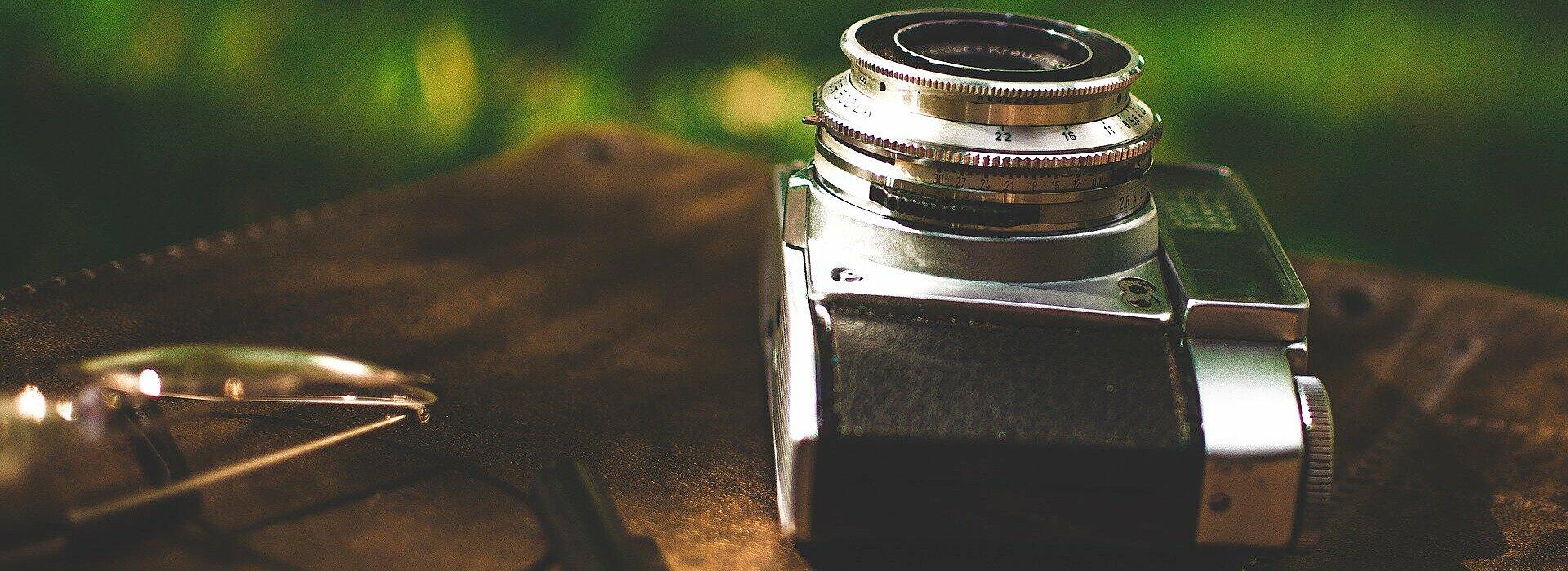 câmera fotográfica antiga sobre mesa de madeira, com uma lupa desfocada em primeiro plano e óculos ao lado.