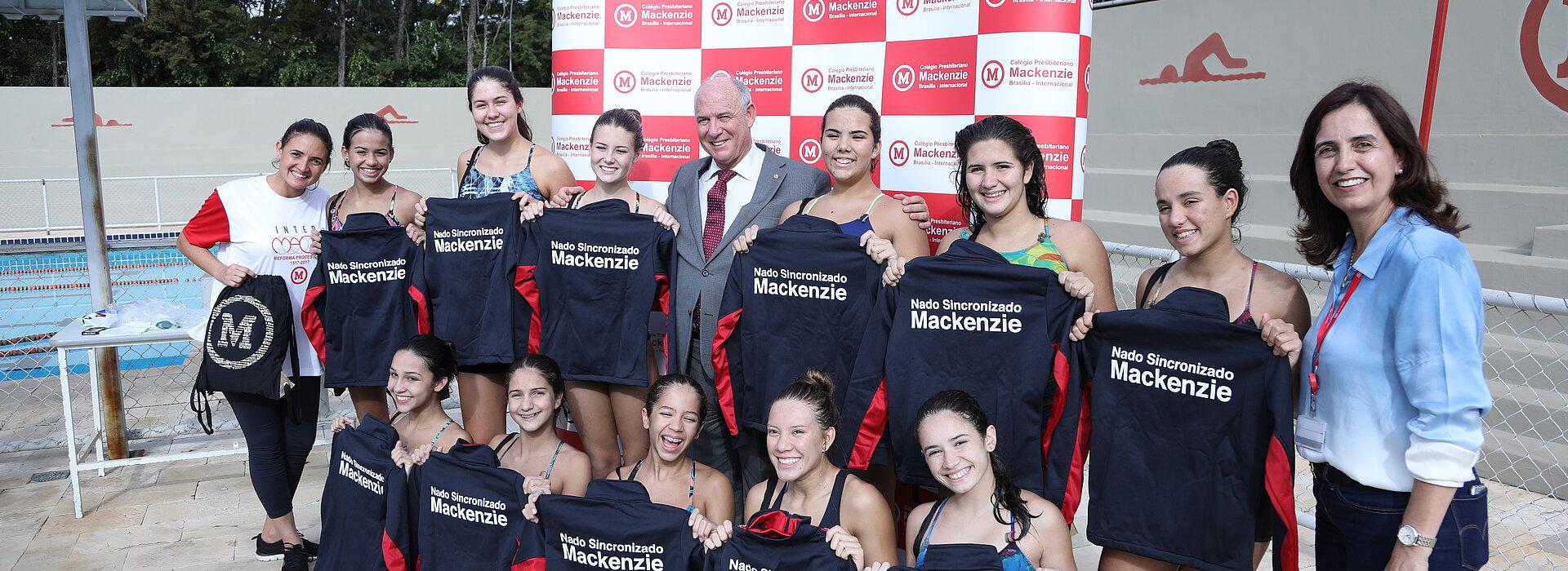 Atletas do nado sincronizado de Brasília enfileiradas em frente à piscina segurando seus agasalhos esportivos pretos do Mackenzie.