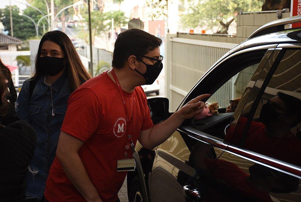 Homem de camiseta vermelha e máscara conversa com motorista de carro da cor preta