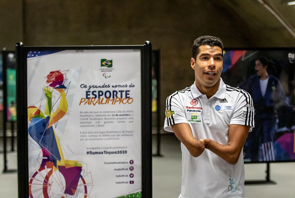 Daniel Dias, ao lado das fotos da exposição