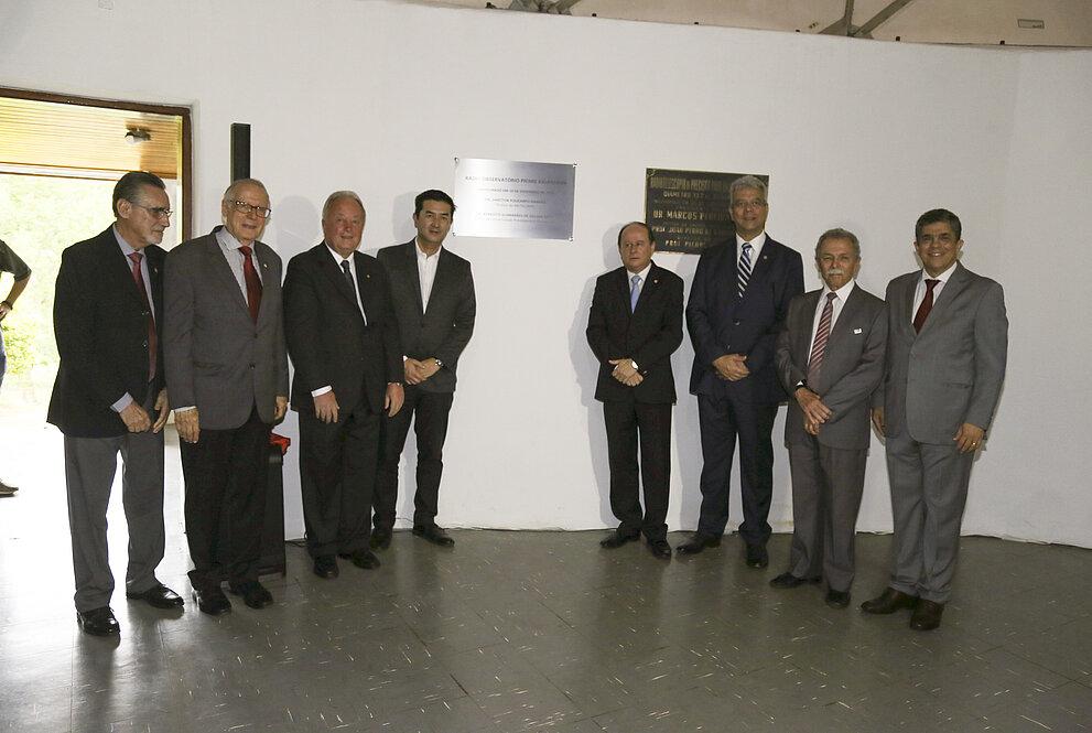 Vários homens brancos em pé exibindo placa de metal