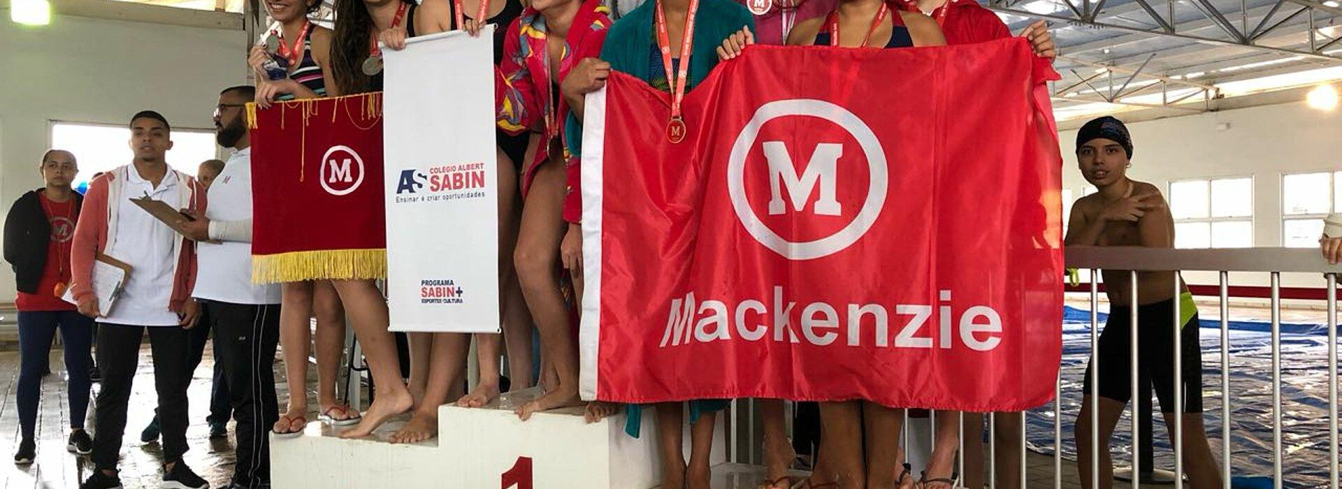 Equipe de natação Mackenzie Brasíliasobre ao pódio.