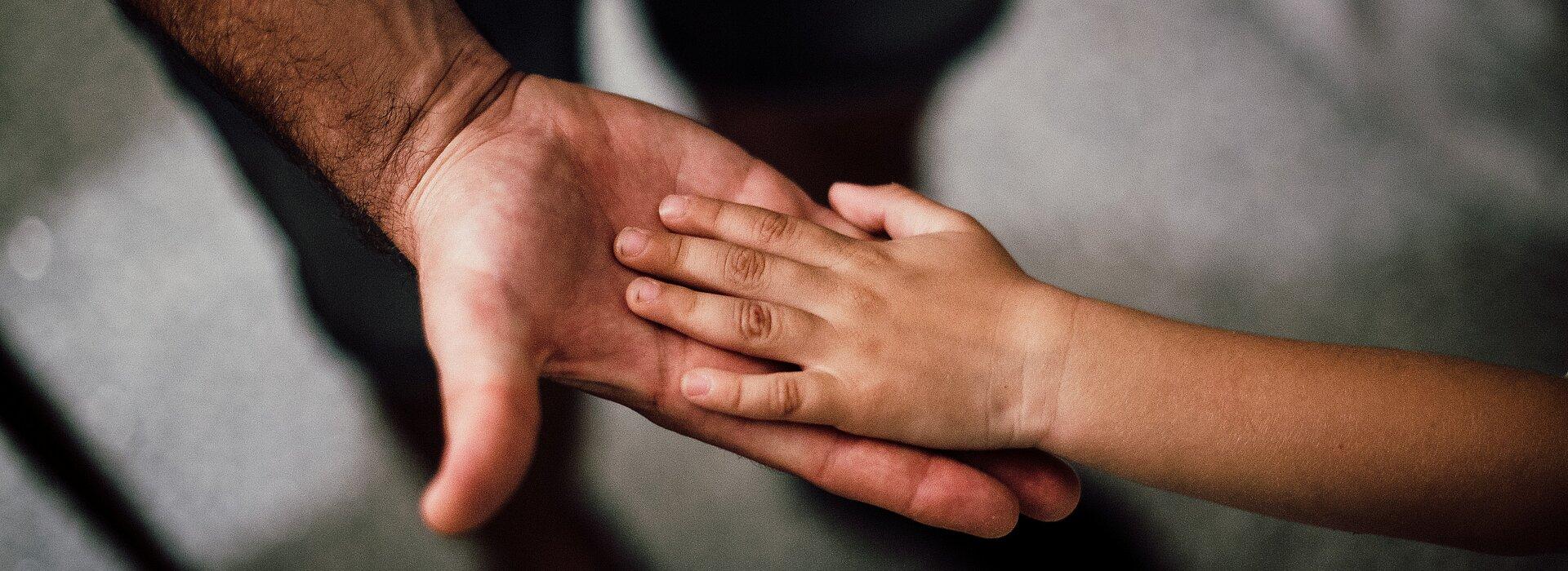 Um adulto estica a mão para uma criança. A foto tem foco na mão deles.