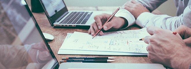 Dois pares de mãos em cima de um conjunto de folhas, que estão no meio de dois notebooks.