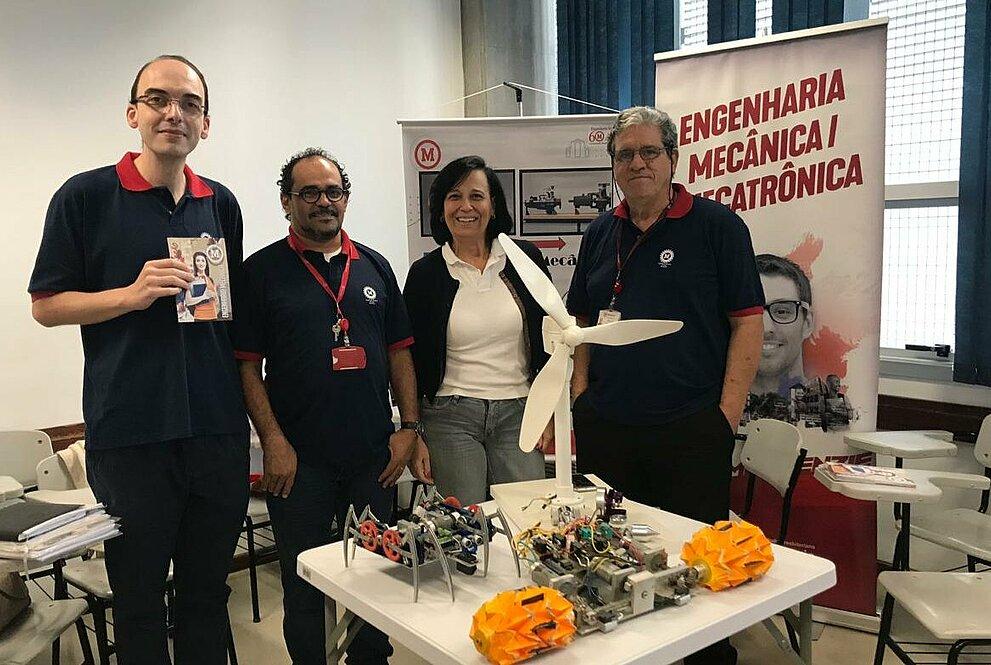 Quatro professores de Engenharia Mecânica reunidos em frente do projeto do curso.