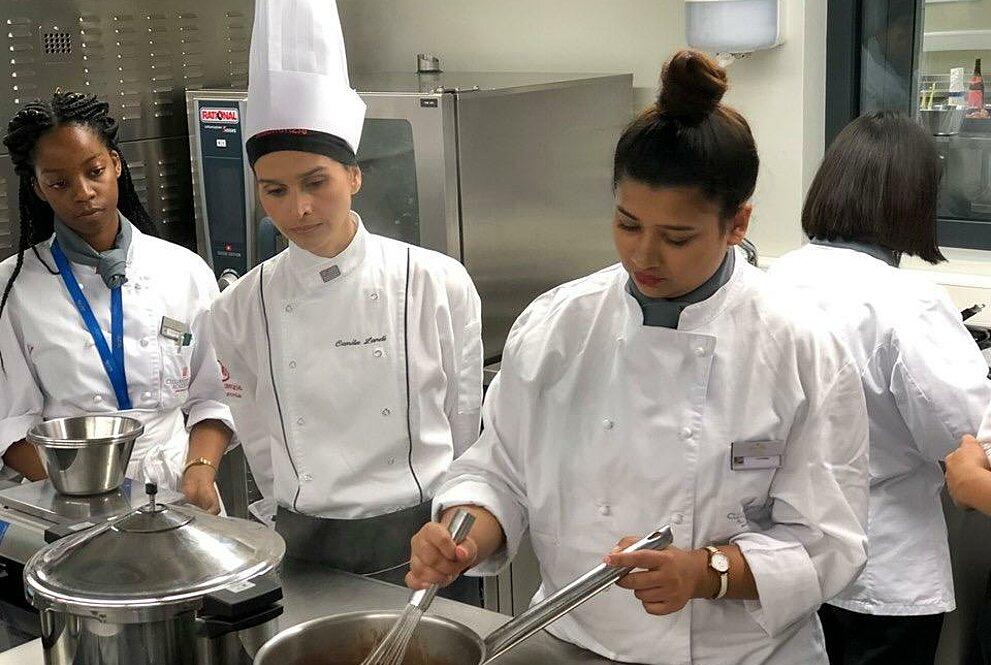 Aluna cozinha com a supervisão de Camila