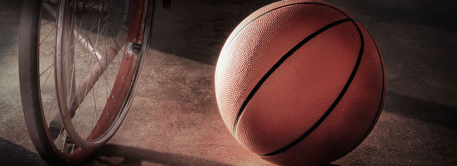 Cadeira de rodas ao lado de bola de basquete.