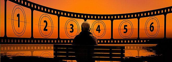 Idoso sentado em um banco de parque, em frente a um lago, com horizonte com vista de rolo de filmes numerado. Foto preta e laranja.
