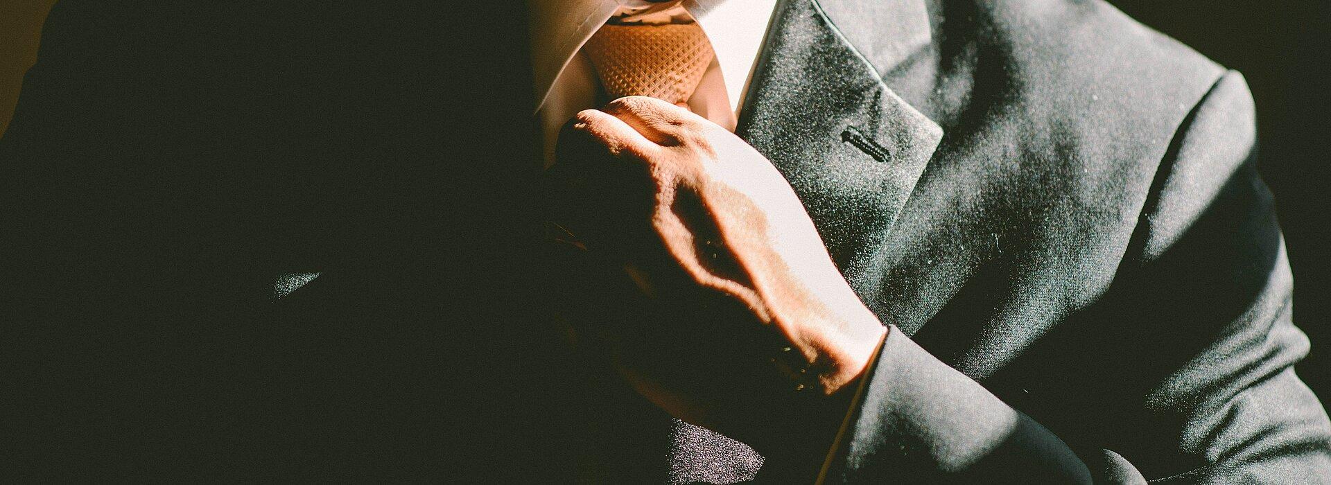 homem ajeitando gravata do terno