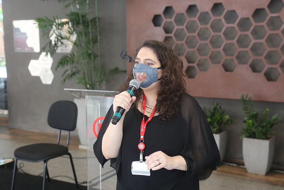 Mulher branca de máscara e roupas em tom preto falando ao microfone