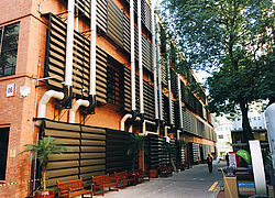 A foto mostra um prédio do campus Higienópolis, com tijolos e detalhes em preto. Uma árvore está do lado direito da foto.