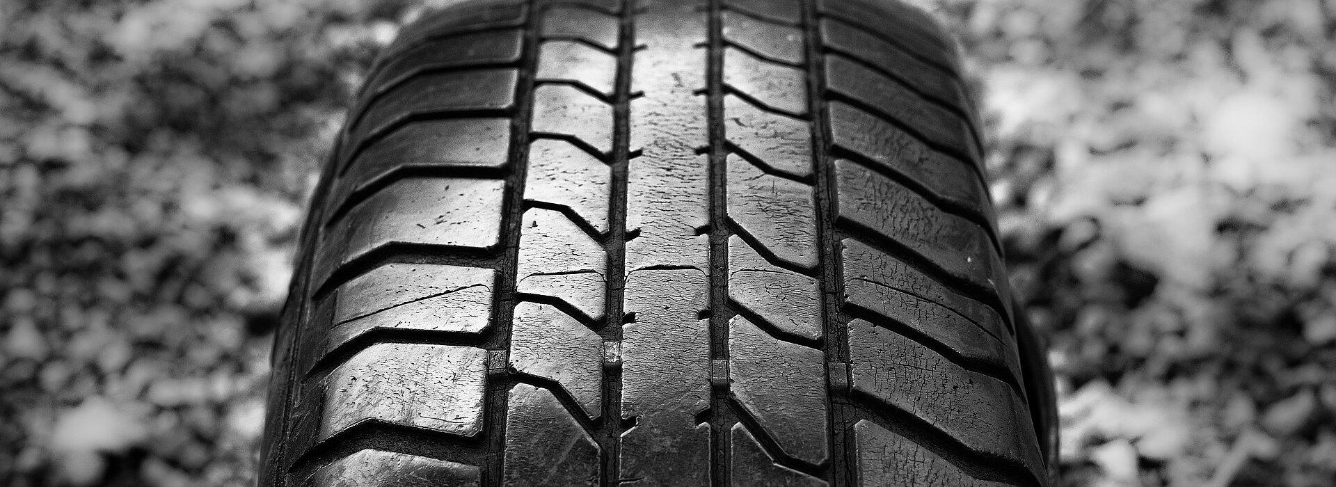 foto de um pneu contra um chão de pedregulhos - imagem em preto e branco