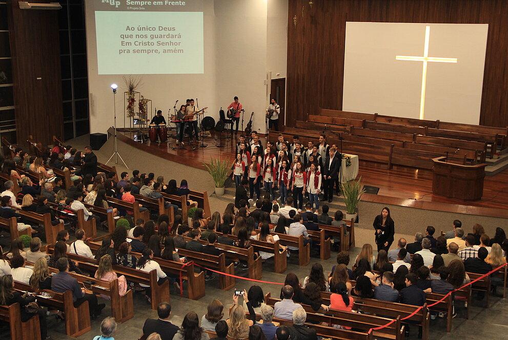 Pessoas assistem à apresentação do coral durante culto