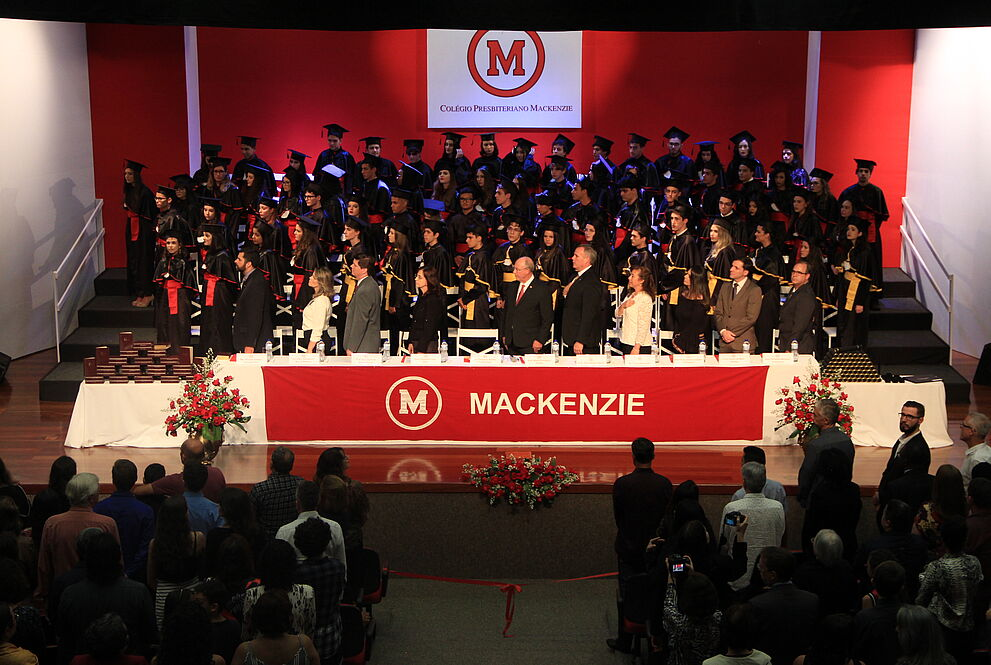 Mesa de autoridades com alunos formandos ao fundo.