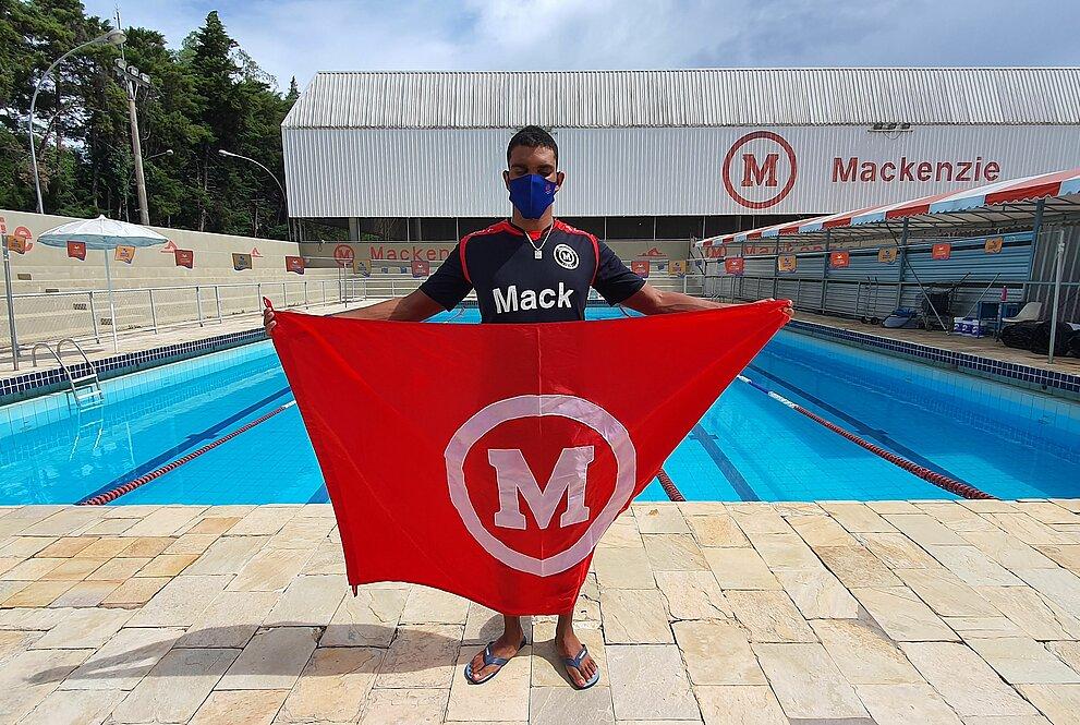 Um homem jovem segurando uma bandeira em frente a uma piscina