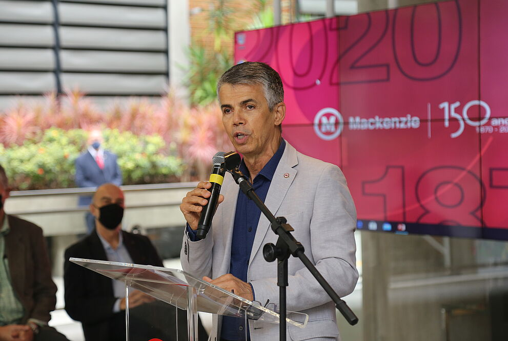 Homem em pé falando ao microfone