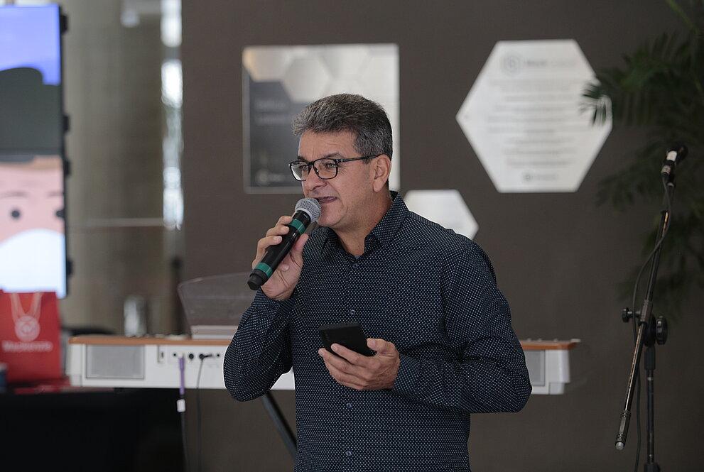 homem branco de camisa em tom escuro, usando óculos e segurando um microfone, fala para plateia