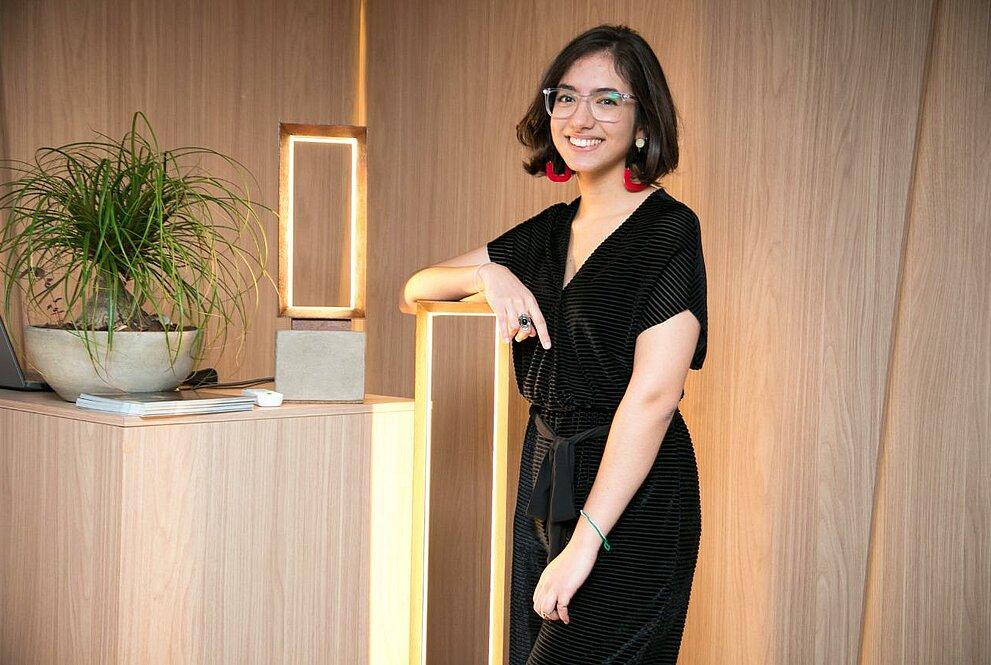 Uma jovem mulher ao lado de uma luminária em formato retangular