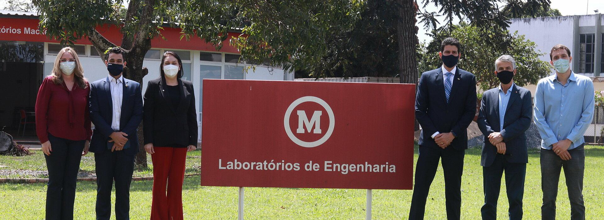 """Seis pessoas, entre homens e mulheres, todos usando máscaras, posam para foto em um jardim de gramado verde ao lado da placa que diz, """"Laboratório de Engenharia"""""""