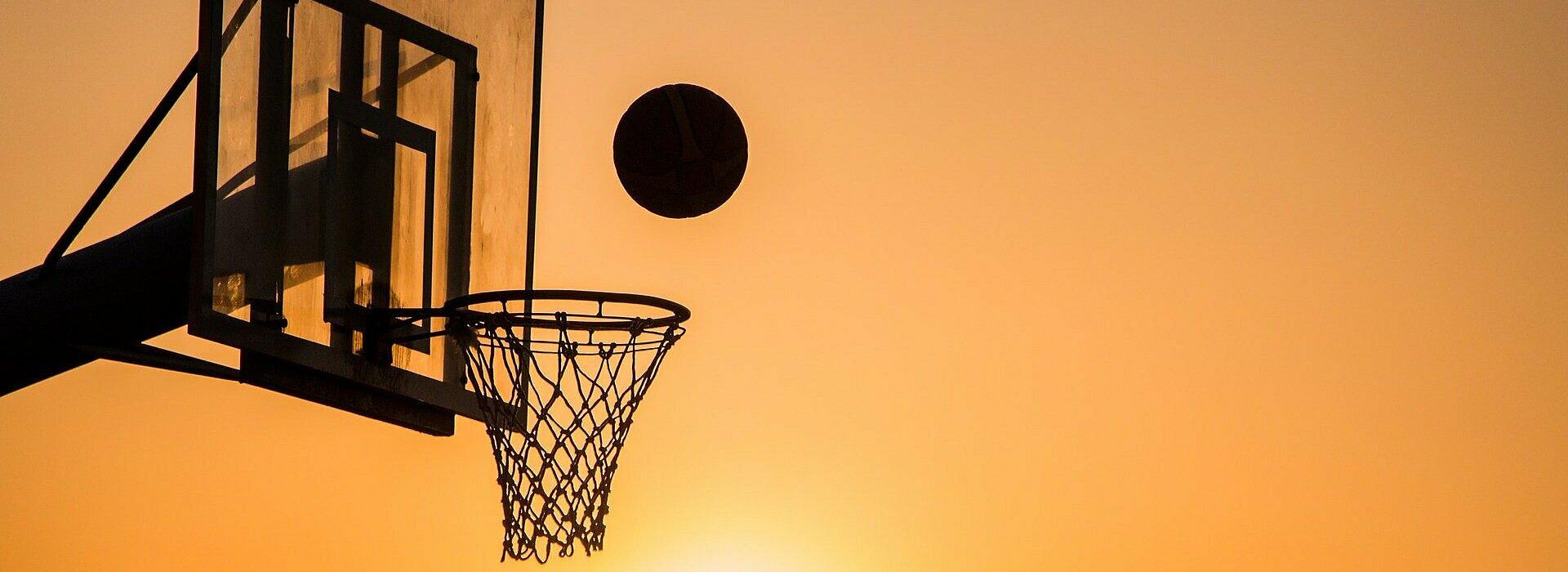 Imagem mostra uma cesta de basquete com um homem jogando a bola em direção a ela.