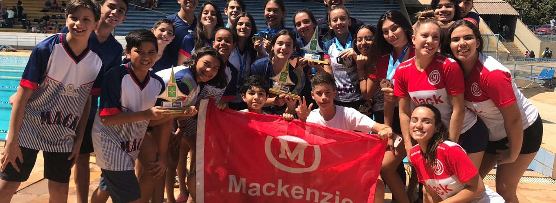 Jovens atletas em pé com bandeira do Mackenzie ao centro