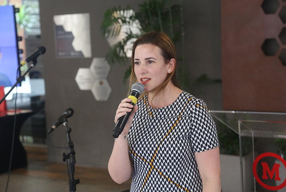 mulher branca com roupa em tons preto e branco, segurando um microfone, se dirige à plateia.